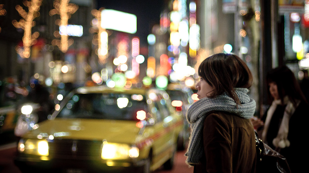 Japanese girl in Tokyo waiting in blurry lights